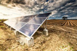 Solar energy panels on a  field under dramatic sky.